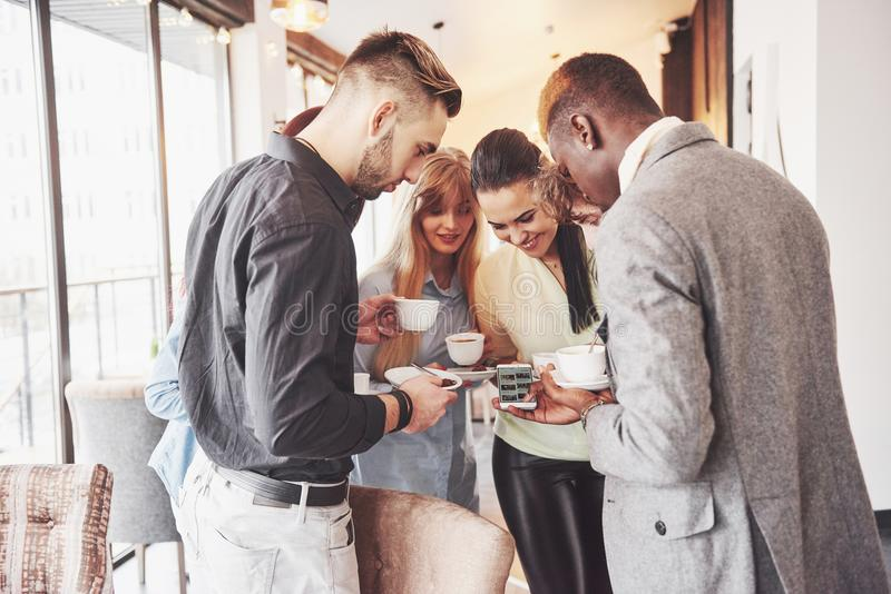 Successful young business people are talking and smiling during the coffee break in office royalty free stock photo