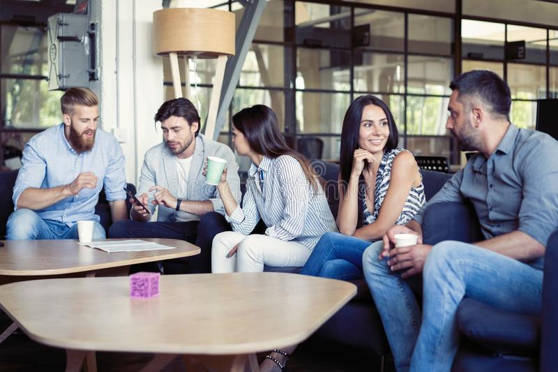 Successful young business people are talking and smiling during the coffee break in office. royalty free stock photo