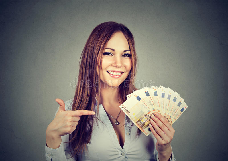 Successful young business woman holding money euro bills in hand. Isolated on gray background. Positive emotion facial expression. Financial reward concept royalty free stock images