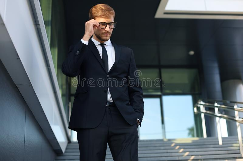 Successful young businessman keeping hand on glasses while walking down the stairs outside the office building stock photography