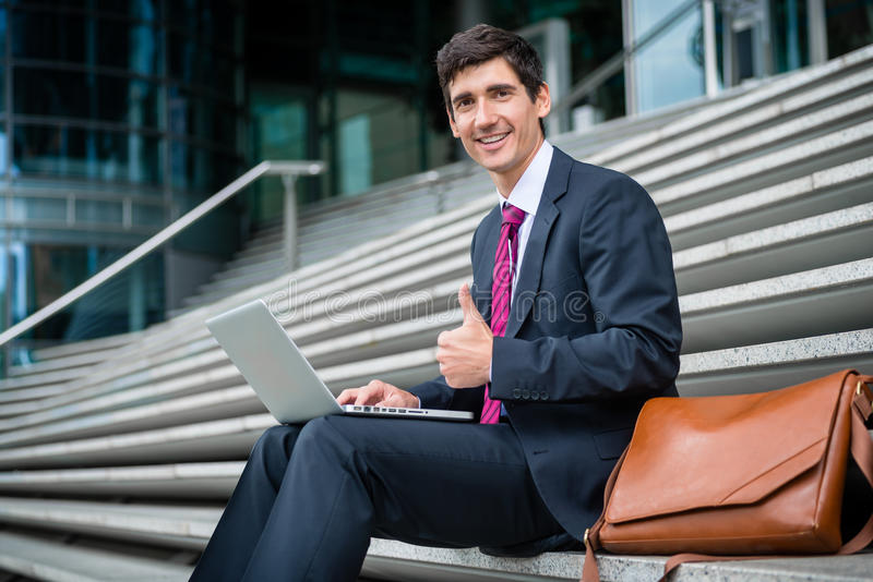Successful young businessman showing thumb up outdoors. Portrait of successful young businessman showing thumb up while working on laptop outdoors stock image