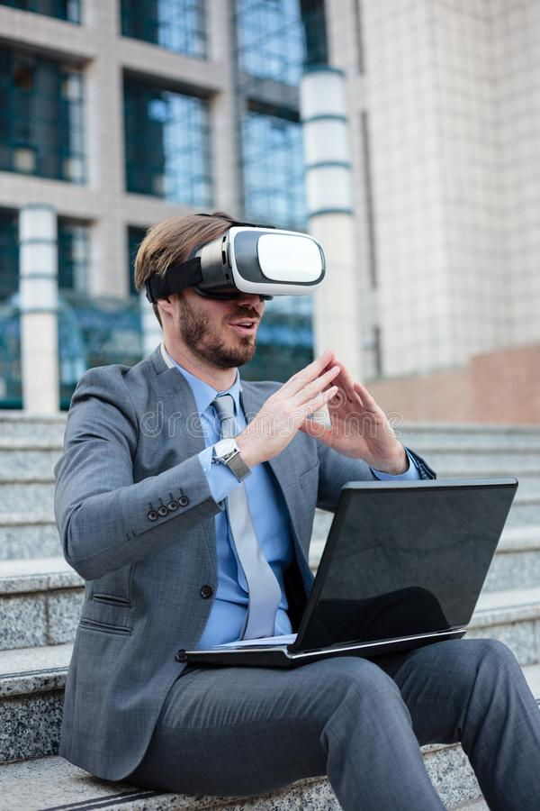 Successful young businessman using virtual reality simulator goggles and making hand gestures, working on a laptop in front of an royalty free stock photography