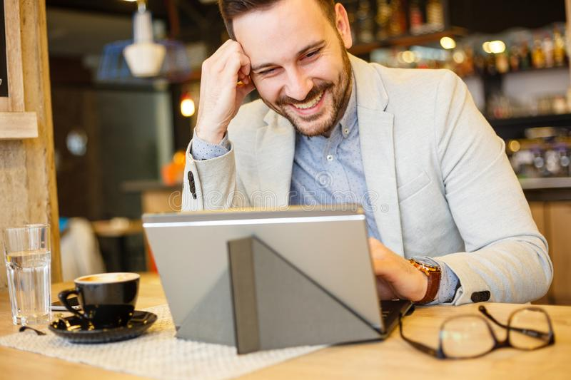 Happy young businessman using a tablet while working in a cafe stock photo