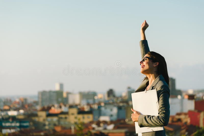 Successful young city business woman raising arm stock photos