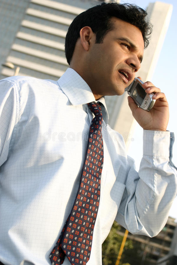 Successful young indian doing business on the move stock photography