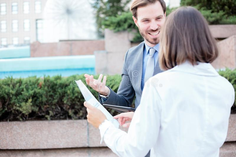 Successful young male and female business people talking in front of an office building, having a meeting and discussing. Looking at each other. Woman is stock images