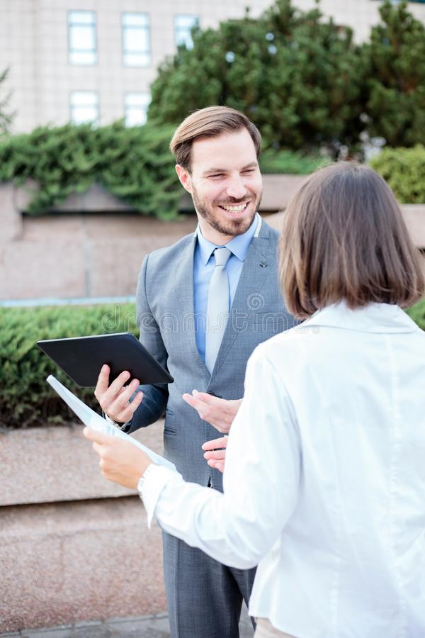 Handsome young male and female business people talking in front of an office building, having a meeting and discussing. Successful young male and female business stock images