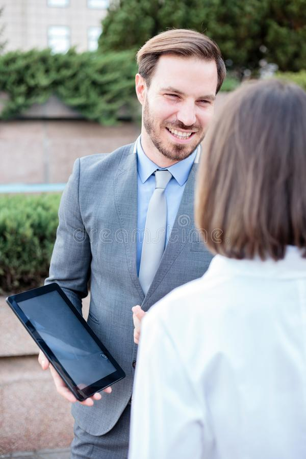 Handsome young male and female business people talking in front of an office building royalty free stock images