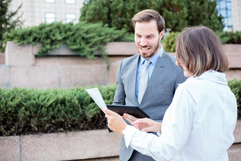 Young male and female business people talking in front of an office building, having a meeting and discussing royalty free stock photos