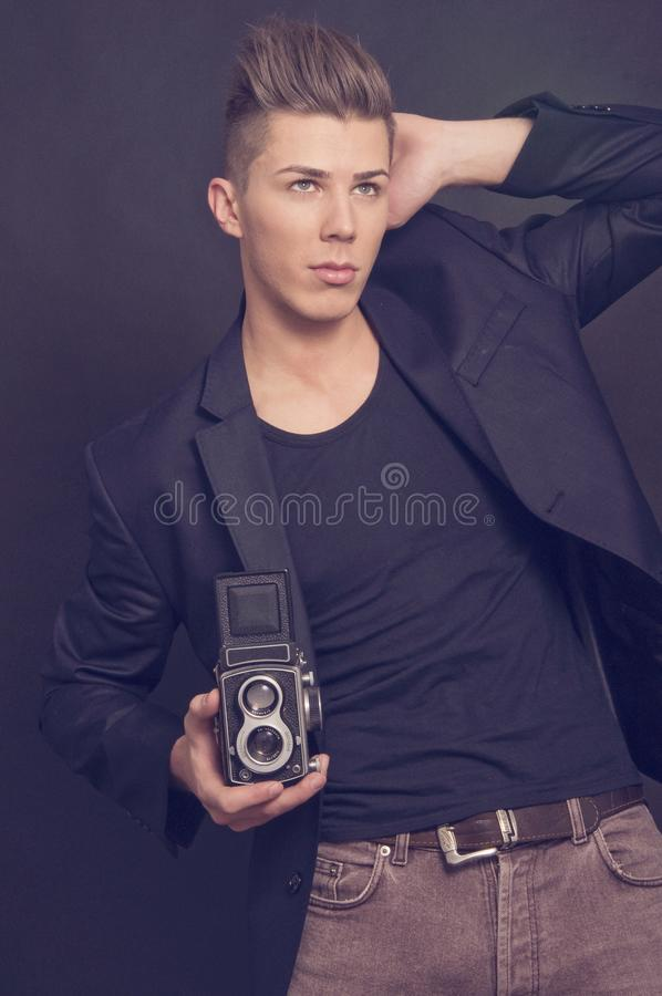 Successful young man on black backgound. Successful young elegant men displayed on black backgound with a film camera stock image