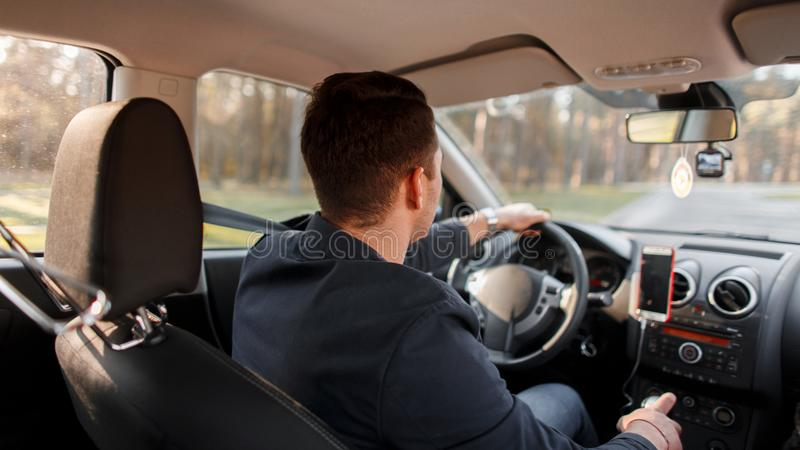 Successful young man drives a car on a sunny day. stock photography