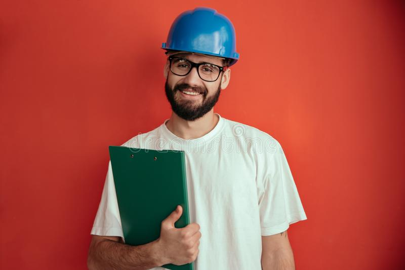 Successful young man engineer in protective helmet and white shirt holding clipboard with document and pen in isolation stock photography