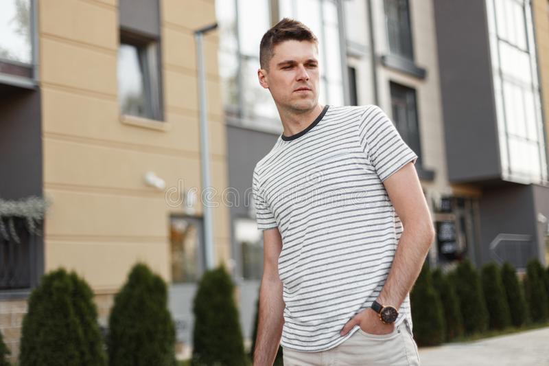 Successful young man freelancer in a stylish T-shirt with a clock stands on a street in the city near a modern building stock photos
