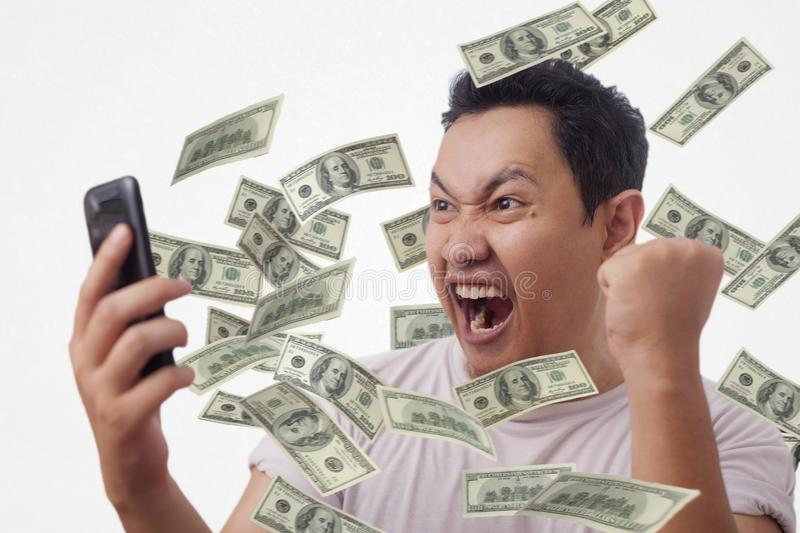 Successful Young Man Getting Money From His Smart Phone royalty free stock image