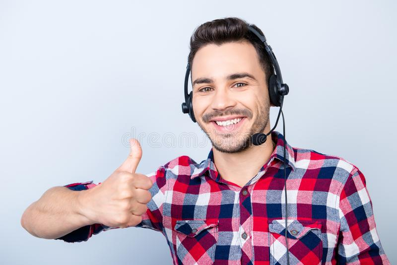 Successful young man operator of a telemarketing is smiling, wearing a headset. He is isolated on a pure light. Background, showing like sign stock photo