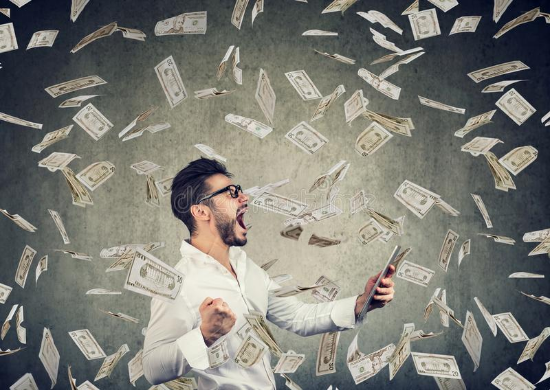 Successful young man using tablet building online business earning money. Dollar bills cash falling down. Beginner IT entrepreneur success economy concept royalty free stock images