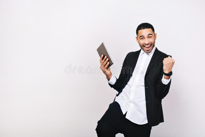 Successful young man in white shirt, black jacket expressing positivity to camera on white background. Leadership, great stock images