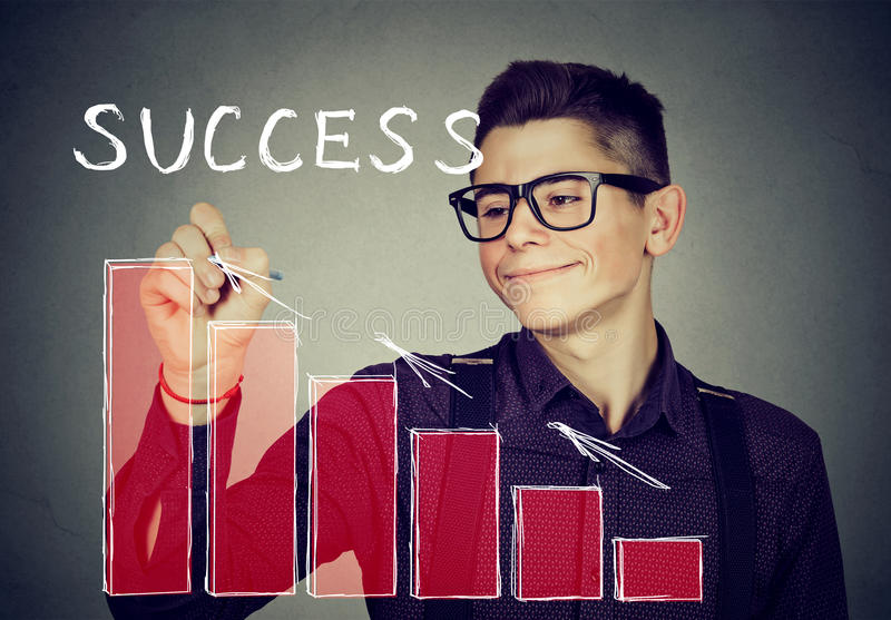 Successful young man writing with pen stock images