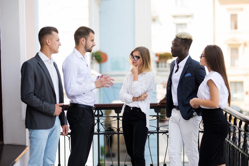 Successful young multiethnic business people are talking and smiling during the coffee break in office royalty free stock image