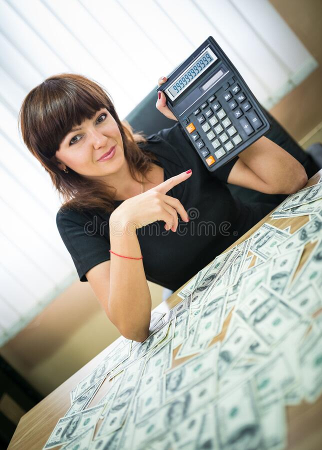 Successful young pretty woman shows on calculator stock photography