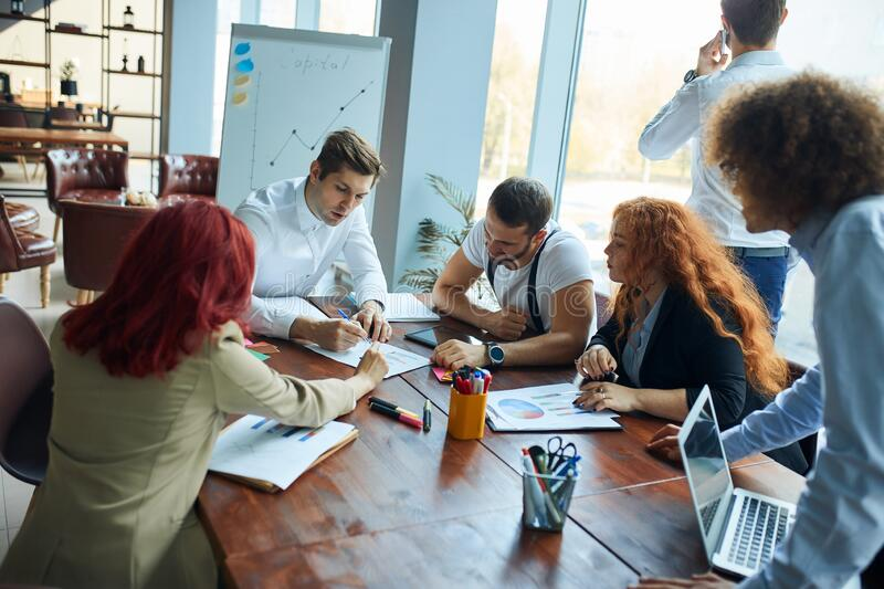 Teamwork process of young team of caucasian coworkers making great business discussion in modern office royalty free stock images