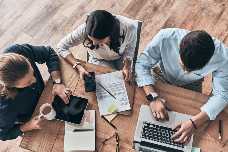 Successful and young. Top view of young modern colleagues in smart casual wear working together while spending time in the office royalty free stock images