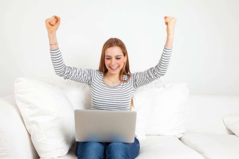 Successful young woman with notebook on a sofa. Young woman with notebook on a sofa is happy about a successful bidding on a online auction royalty free stock photography