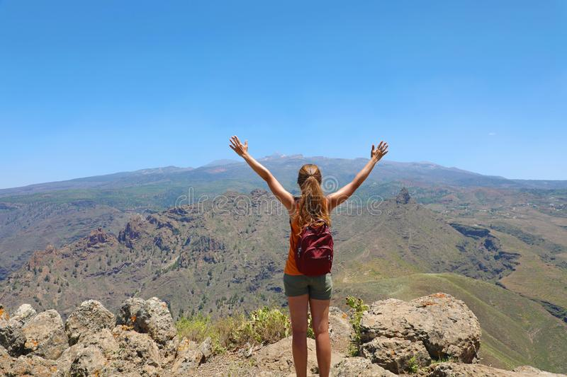 Happy young hiker woman with open arms raised on mountain peak stock image