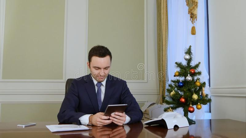 Successfull businessman using a tablet to send E-mail congratulation over the Internet. Professional shot in 4K resolution. 055. You can use it e.g. in your stock photo