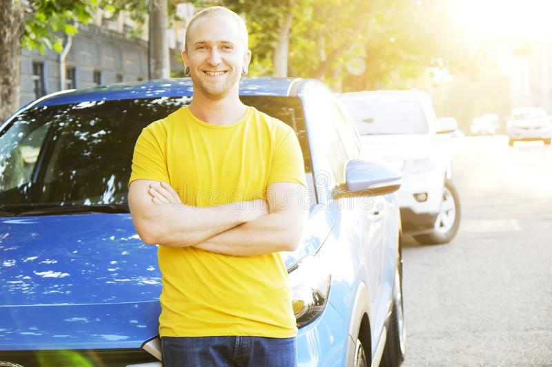 Successfull happy young man and his car in soft sunset light on urbanistic background. Busines man with vehicle on roadside. stock images