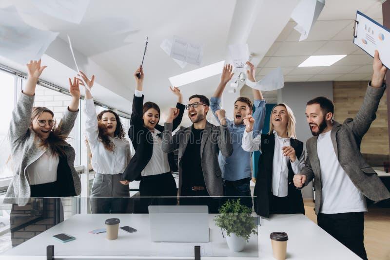 Successo e concetto di conquista - gruppo felice di affari che celebra vittoria in ufficio fotografia stock libera da diritti