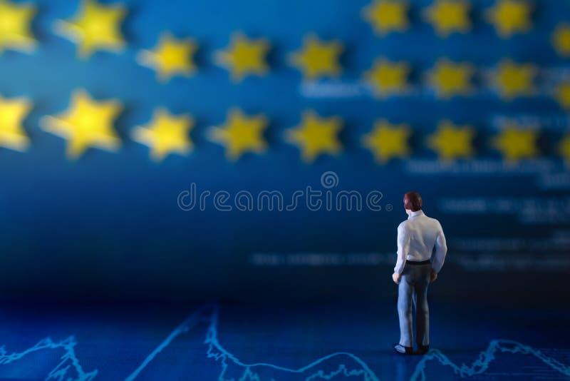 Successo nel concetto di talento o di affari una condizione miniatura dell'uomo d'affari sul grafico finanziario e considerare la fotografie stock libere da diritti