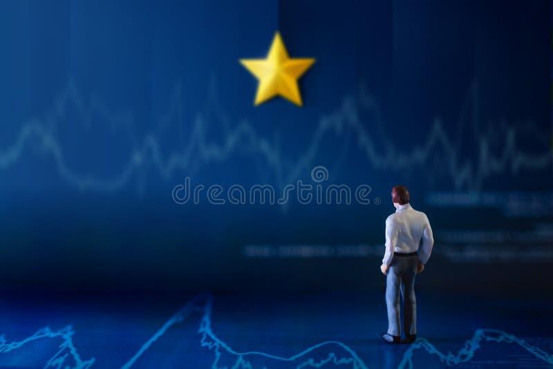 Successo nel concetto di talento o di affari una condizione miniatura dell'uomo d'affari sul grafico finanziario e considerare la immagine stock