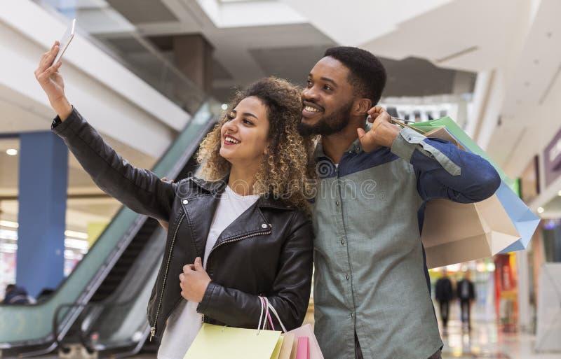Succesvol Afrikaans paar die selfie na het winkelen in wandelgalerij maken stock foto's
