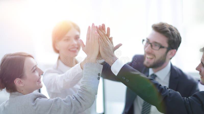 Succesvol commercieel team die elkaar hoog-vijf geven, zich bevindt in het bureau stock fotografie