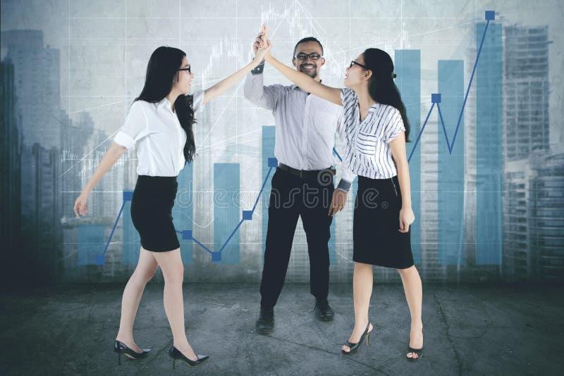 Succesvol commercieel team die hoge vijf handen samen geven stock afbeeldingen