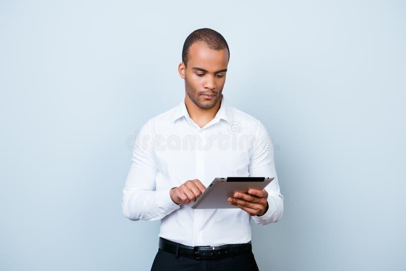 Succesvol denk jonge Afrikaanse kerel doorbladert bij zijn tablet, s na stock fotografie