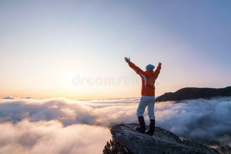 Succesvol sportief meisje staat aan de rand van het neerslag Het berglandschap in de moerige ochtend Sunrise herfst royalty-vrije stock afbeeldingen