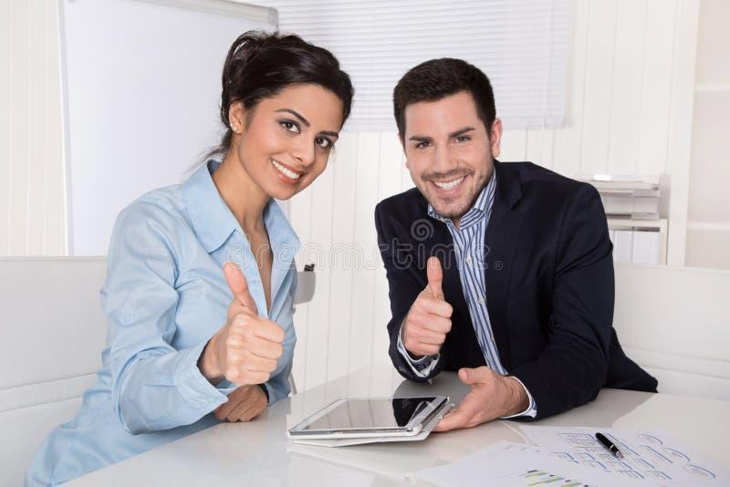 Succesvol team met duimen omhoog op kantoor. stock fotografie