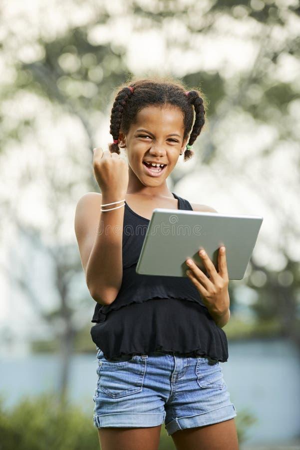 Succesvol tienermeisje die tablet gebruiken stock afbeeldingen
