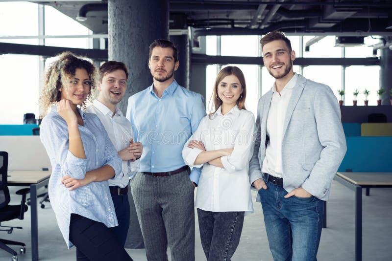 Succesvol vriendschappelijk team met gelukkige arbeiders in bureau stock fotografie