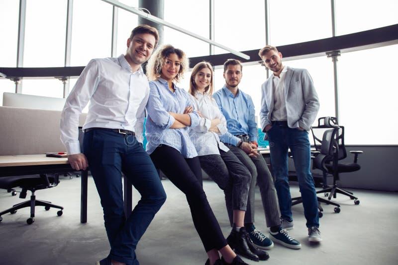 Succesvol vriendschappelijk team met gelukkige arbeiders in bureau royalty-vrije stock fotografie