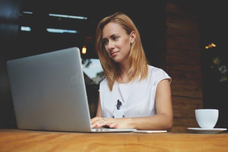 Succesvol wijfje die freelancer netto-boek voor het afstandswerk gebruiken tijdens ochtendontbijt in koffie stock foto
