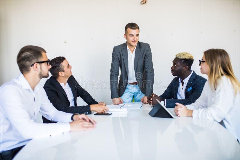 Succesvol zakenman chef- voorstellend nieuw project aan werknemers bedrijfsbus im kostuum die presentatie geven aan cliënten in v stock foto's