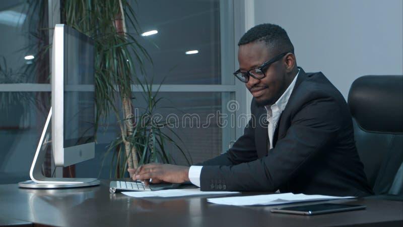 Succesvolle Afrikaanse Amerikaanse zakenmanzitting bij bureau, die aan generische laptop werken, die een bericht typen stock foto's