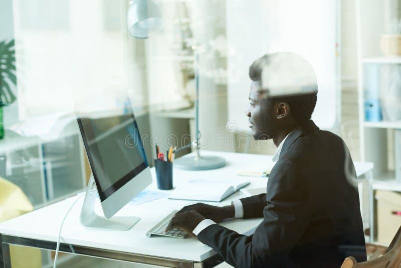 Succesvolle Afrikaanse Zakenman die PC met behulp van royalty-vrije stock foto