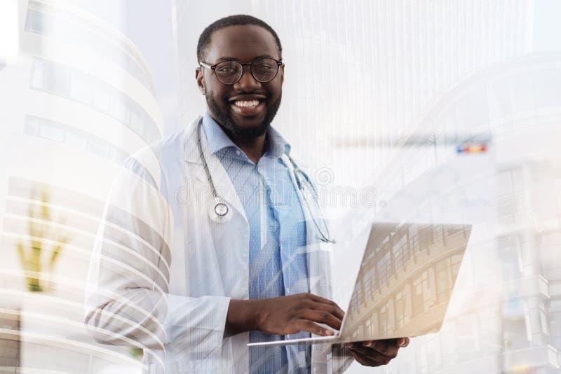 Succesvolle arts die laptop in handen houden stock foto