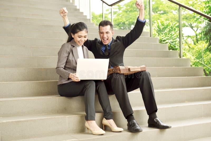 Succesvolle Aziatische bedrijfsmensen die met laptop zeer gelukkig kijken stock afbeelding