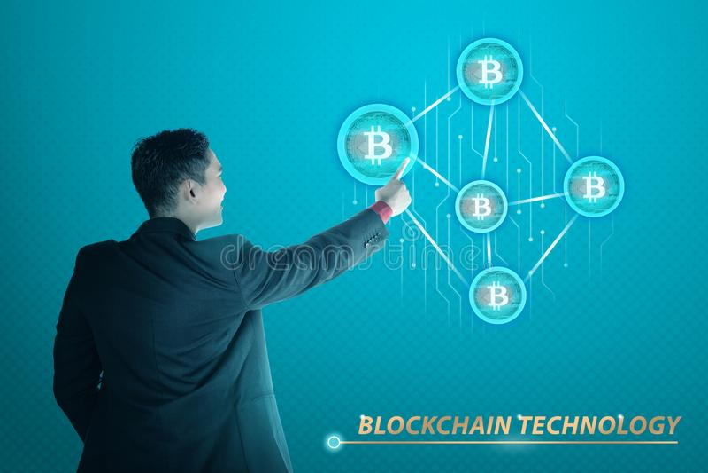 Succesvolle Aziatische zakenman wat betreft het pictogram van het bitcoinnetwerk stock foto's