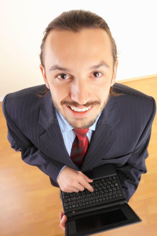 Succesvolle bedrijfsmens met laptop in handen. stock foto